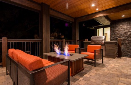 Covered paver deck with firepit in The Reserve
